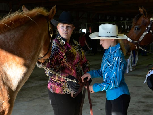 Mariah Berg passes the reigns of her horse to Ciara Ewald, the daughter of her friend John Ewald, at the Manitowoc County Expo on Sunday, May 29. Berg helped Ewald through several halter class competitions and also let her show her horse, Lala, throughout the day.