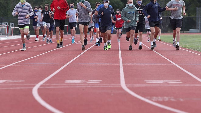 Members of the Hingham High boys cross-country team warm up on the school track.