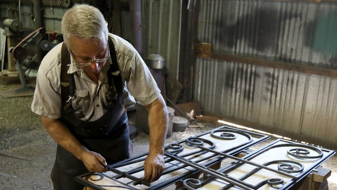 In this Friday July 21, 2017 photo, Scott Wadsworth works on a project in his Roseburg, Ore shop. Wadsworth has been fascinated by blacksmiths since he was 12 years old, when he kept running across descriptions of them in the Western books he enjoyed.