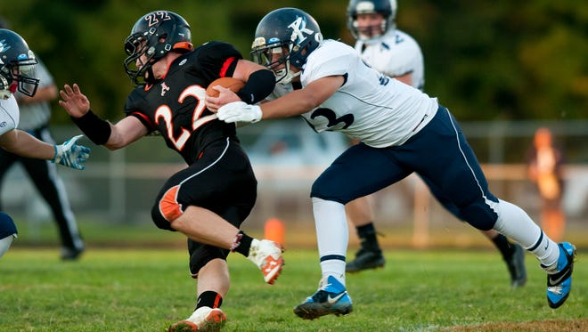 Richmond junior Spencer Trapiss tackles Almont senior Nick Baker during Friday night's action at Almont High School.