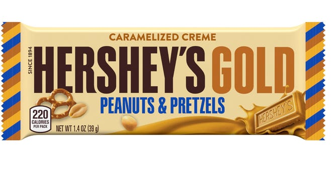 This image released by Pennsylvania-based The Hershey Company shows their new candy bar Hershey's Gold that will go on sale Dec. 1, 2017. It's described as a caramelized cream bar embedded with salty peanut and pretzel bits.