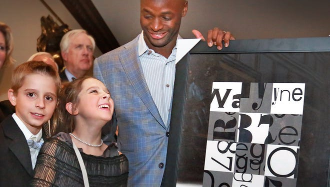 Artist Sophie Collier, 13, a heart patient at Riley Hospital for Children, and her brother Bryson stand with one of their heroes, Colts receiver Reggie Wayne. Sophie and Bryson presented a special work they did just for Wayne during the opening of Forty Two.