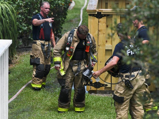 Firefighters work to extinguish a house fire at 3240
