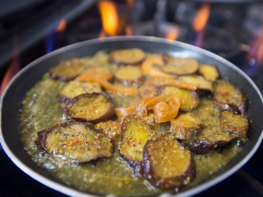 Burrani, an eggplant dish served with sauce, is prepared