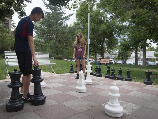 Johnathan Rawlings plays a game of chess with Maya Carlson outside Old Town Library on Tuesday, June 13, 2017.
