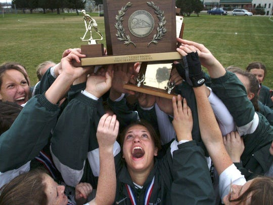 Stowe High School's Madison Ross (center) holds the girls Division III field hockey championship trophy after the Raiders won the 2004 title.