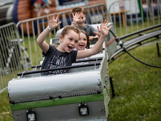 June Kinney, 8, of San Tan Valley, Arizona, holds up her arms while riding a small roller coaster during the Croswell Fair Wednesday, June 15, 2016 at the fairgrounds in Croswell.