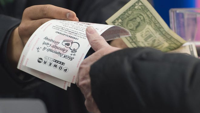 A man purchases a Powerball lottery ticket at a liquor store in Washington, DC, January 4, 2016. Lottery officials predict the January 6 jackpot will reach $400 million, one of the largest in the game's history. AFP PHOTO / SAUL LOEBSAUL LOEB/AFP/Getty Images