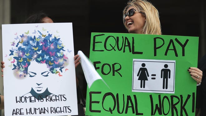 Elana Goodman and other express their views March 14 in Florida. In New Mexico, women who work full-time are earning about 82 percent of what men are paid, according to a 2016 survey.