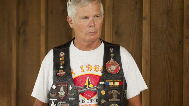 Jay Kimbrough stands in Yankee's Tavern in the community of Carlos, in western Grimes County, in 2012, wearing a motorcycle vest that commemorated his service in Vietnam.