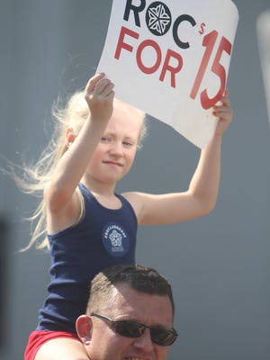 In this file photo, Metro Justice marchers Juliana Shattuck, 6, of Rochester sits on Chris McCamic's shoulders holding a minimum wage sign asking for $15.