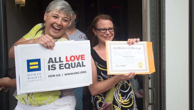 Jessica Dent, left, and Carolee Taylor, right, show their marriage license at the Montgomery County Courthouse on Friday, June 26, 2015 in Montgomery, Ala. Gay and lesbian Americans have the same right to marry as any other couples, the Supreme Court declared Friday in a historic ruling deciding one of the nation's most contentious and emotional legal questions. Celebrations and joyful weddings quickly followed in states, including Alabama, where they had been forbidden. (Albert Cesare/The Montgomery Advertiser via AP)  NO SALES; MANDATORY CREDIT