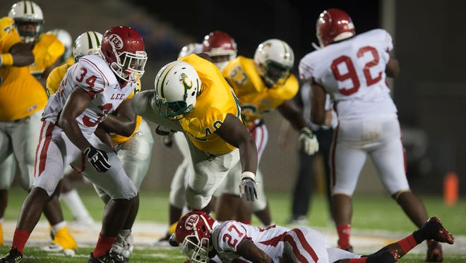 Carver running back Daron Jenkins (40) is tackled by Lee linebacker Kentavious Franklin (34) and Antonio Ballard (27) during the game between Lee High School and Carver High School on Thursday, Aug. 27, 2015, at the Cramton Bowl in Montgomery, Ala.