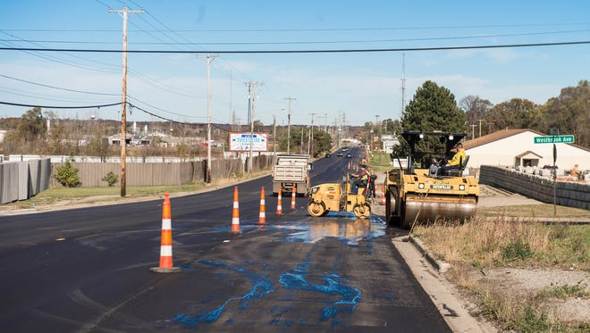 Workers finishing paving work on Raymond road on Monday.