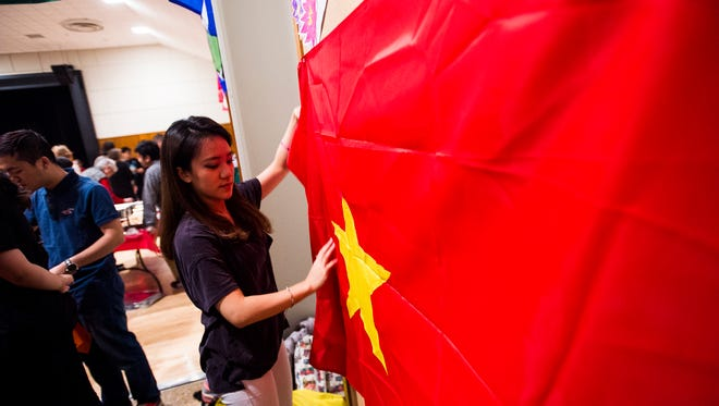 Tien Dao, a freshman student at Gettysburg College, hangs the Vietnamese flag at the Vietnamese cuisine booth during the second annual BurgBurst on Saturday Dec. 5, 2015 at Gettysburg College.