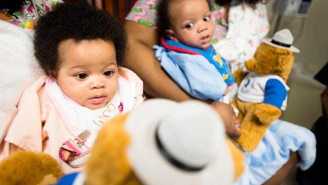 Serenity Stevenson, left, and her twin Sameer, five-month-olds, look at teddy bears brought to them for Christmas by the Alabama State Troopers on Tuesday, Dec. 22, 2015, at Baptist Medical Center South in Montgomery, Ala.