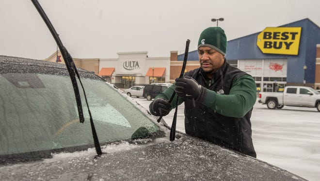 Jaris McIntosh cleans the ice and sleet off of his wiper blades due to Monday's bad weather.
