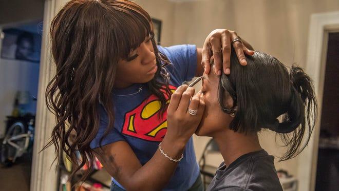 Ebony Roberson uses an eyebrow pencil on her client Canice Jame.