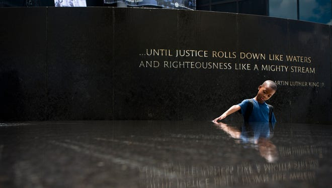 Benjamin Levett, 6, touches the Civil Rights Memorial fountain during a memorial to honor civil rights leader Julian Bond held by the Southern Poverty Law Center on Saturday, Aug. 22, 2015 in Montgomery, Ala.