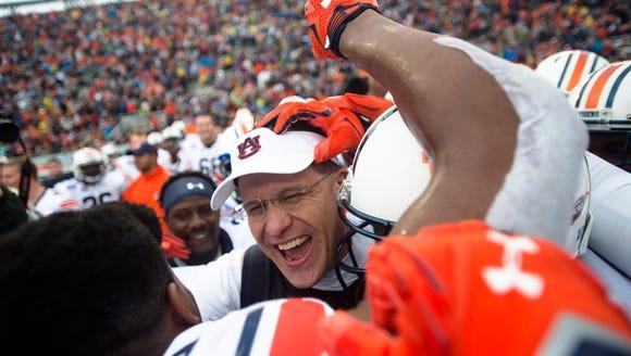Auburn head coach Gus Malzahn embraces Auburn linebacker