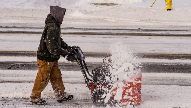 In this 2016 photo, a maintenance worker uses a snow blower to clear off sidewalks along Capital Ave. SW.