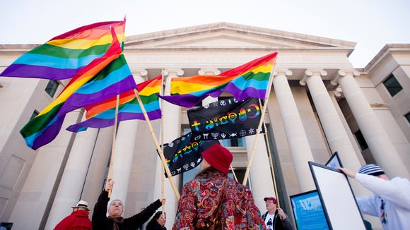 "Minoo Vafai, left, holds a rainbow flags with others during the ""Remove Roy Moore Rally"" on Tuesday, Jan. 12, 2016, outside the Alabama Supreme Court building in Montgomery, Ala."