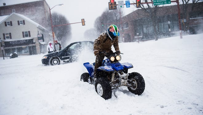 An ATV rider sprays snow into the air before taking off in Center Square on Saturday Jan. 23, 2016 in downtown Hanover, Pa.
