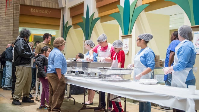 Patrons line up for a hot meal from God's Kitchen at the First Congregational Church.