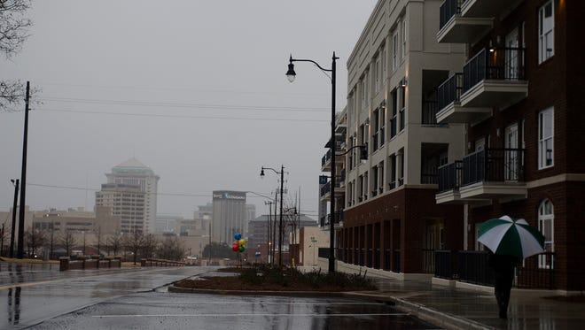 A man walks through the rain in downtown Montgomery, Ala., on Monday, Feb. 15, 2016.