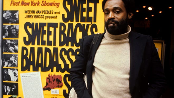 """Melvin Van Peebles posed with a movie poster for """"Sweet Sweetback's Badasssss Song"""" during the film's 1971 screenings in New York."""