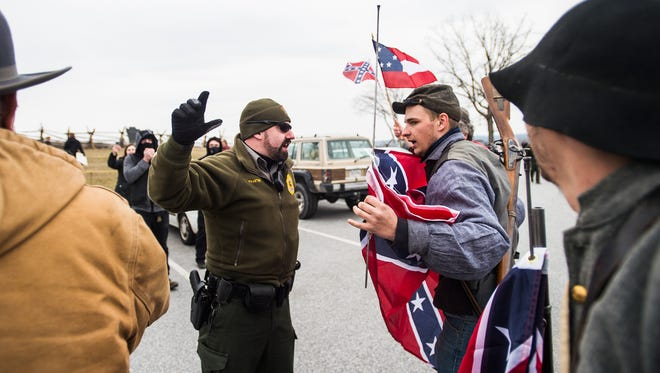 Park Rangers with Gettysburg National Military Park prevent Confederate flag supporters from getting near a group of counter-protesters during the Confederate flag day at the Eternal Peace Light Memorial in Gettysburg, Pa., Saturday, March 5, 2016. (Shane Dunlap/The Evening Sun via AP)