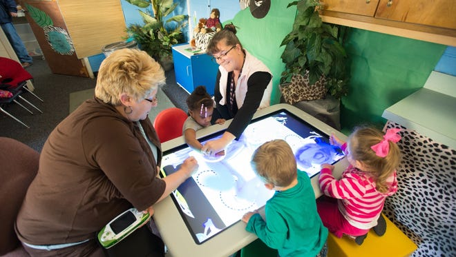 Debra Heath, who teaches 2-year-olds, and instructional technology teacher Kerry Merrell, help children use the smart table at T.R. Jackson Pre-K center in Milton. The readiness rates for T.R. Jackson and other centers across the state won't be released for the second consecutive year because of questions about the readiness test.