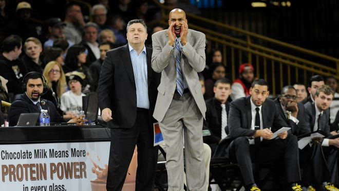 Lansing's Saddi Washington, front, who spent the last decade as an assistant coach at Oakland University, was hired Wednesday as an assistant  coach at the University of Michigan. At Oakland, he coached under Greg Kampe, left, and recruited, coached and coached with Drew Valentine, seated right.