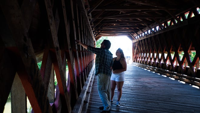 Steven Broomes and Alyssa Barefield from Carroll County explore graffiti written on the walls of Sachs Covered Bridge over Marsh Creek on Thursday July 21, 2016 near Gettysburg.