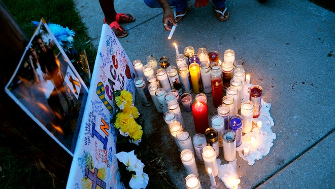 Candles are relit during a vigil for brothers Angel Berrios, 21, and Abdiel Vazquez-Soto, 19, who died in a late-night shooting and car crash in 2015.