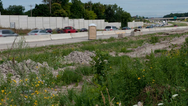 Dirt piles from sound wall construction line northbound US-127 near Saginaw Highway on Aug. 5.