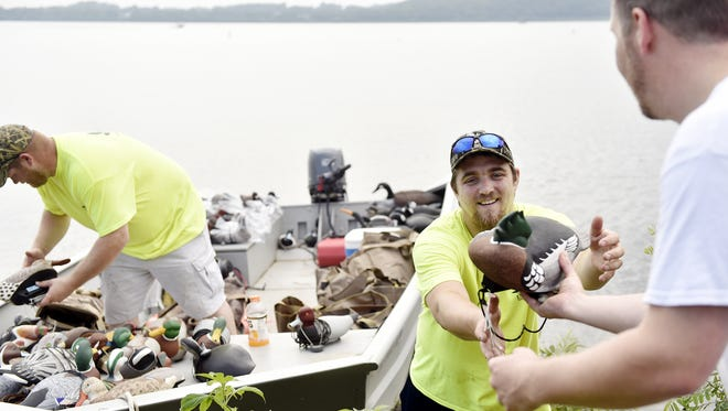 From left, Delta Waterfowl Foundation members Shawn Benner, Jason Sanderson and Todd Bergman load a boat with waterfowl decoys for a contest on the Susquehanna River. The river is a popular destination for boating, fishing and other recreational activities.