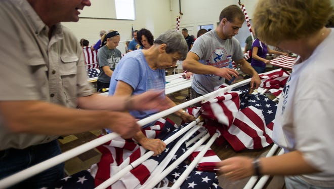 Volunteers from left, Edwin Tharp, of Glenville, Kathy Adams, of Hanover and Clint Wright, of Glenville, work on assembling flags Saturday Aug. 13, 2016 at the West Manheim Township building. Over 50 volunteers assembled 3,000 flags on Saturday. The American flags will be used in the 9/11 Healing Field Memorial in September.