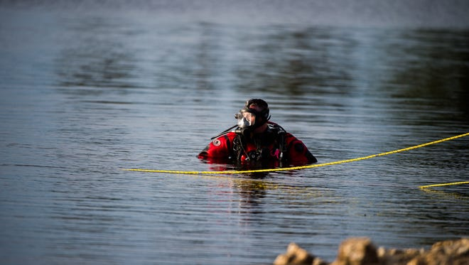 Divers with the Penn Township dive team search for a submerged pickup truck that drifted into the Longarm Reservoir on Tuesday..