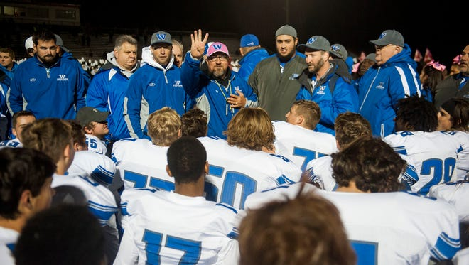 Walled Lake Western coaches speak with the team after with win against Brighton on Friday.