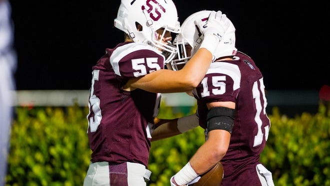 First Baptist Academy's Jayce Howell(15) celebrates with his team mate Daniel Marquina(55) during a game against St. John Neumann in Naples, Fla., on Friday, Oct. 21, 2016.