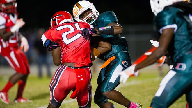 Dunbar High School's Seneca Millidge (9) wraps up Immokalee's  Tyrique Toussaint (21) during a game against Immokalee in Fort Myers, Fla., on Monday, Oct. 31, 2016.