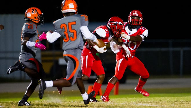 Immokalee High School's Jean Sanon (10) runs into his teammate Shedro Louis (20) after catching a deep pass during a game against Lely High School in Fort Myers on Monday, Oct. 31, 2016.