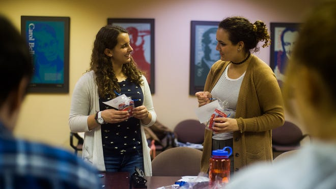 Senior Piper O'Keefe, left, chats with fellow Gettysburg College Democrats member and freshman Gabrielle Killian, right, while creating Democrat voting information packages with candy to hand out to registered Democrats on Gettysburg College campus before Election Day during a group meeting Wednesday night Nov. 2, 2016 at Gettysburg College.