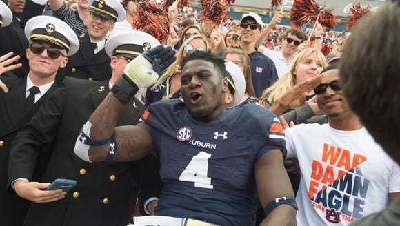 Auburn linebacker Jeff Holland (4) salutes while celebrating