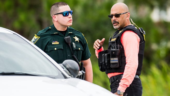 Law enforcement officers work near an Interstate 75 off ramp at Corkscrew Road in Estero, Fla., on Monday, Nov. 14, 2016, after an officer-involved shooting.