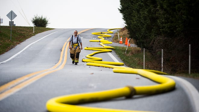 A firefighter walks Jackson Lake Road in Jackson Township as firefighting crews work at the scene of a propane tanker crash Wednesday Nov. 16, 2016.