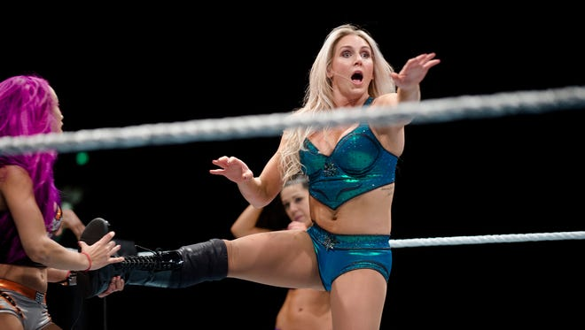 Charlotte Flair reaches for help as Sasha Banks holds her foot up during the WWE Raw Live performance at the Garrett Coliseum in Montgomery, Ala., on Saturday, Jan. 7, 2017.