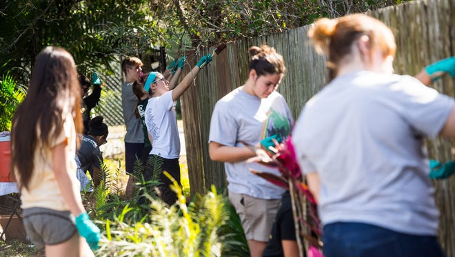 St. John Neumann students paint some fencing at the Collier Preserve in Naples, Fla., on Friday, Feb. 3, 2017. The entire student body of St. John Neumann Catholic High School along with faculty and parents engaged in Christian service projects at twenty-one locations throughout Collier County. The days are being conducted as part of Catholic Schools Week activities. National Catholic Schools Week is the annual celebration of Catholic education in the United States.