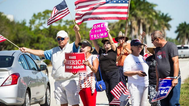 People wave signs and flags at traffic in support of President Donald J. Trump at a pro-Trump rally in Naples on Saturday, March 4, 2017. Many supporters of President Trump held rallies around the Southwest Florida area on Saturday.